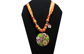This brightly colored necklace has a round metal medallion covered with yellow, purple, blue, orange, pink and white flowers. The sheer fabric has a pattern of various shades of orange with yellow glass painted beads and orange faceted beads. A cute little white flower with rhinestone center charm compliments the medallion.